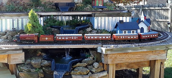 Lionel's G gauge Hogwarts Express with two cars borrowed from another set running on the permanent tracks of my garden railroad. Click for bigger photo